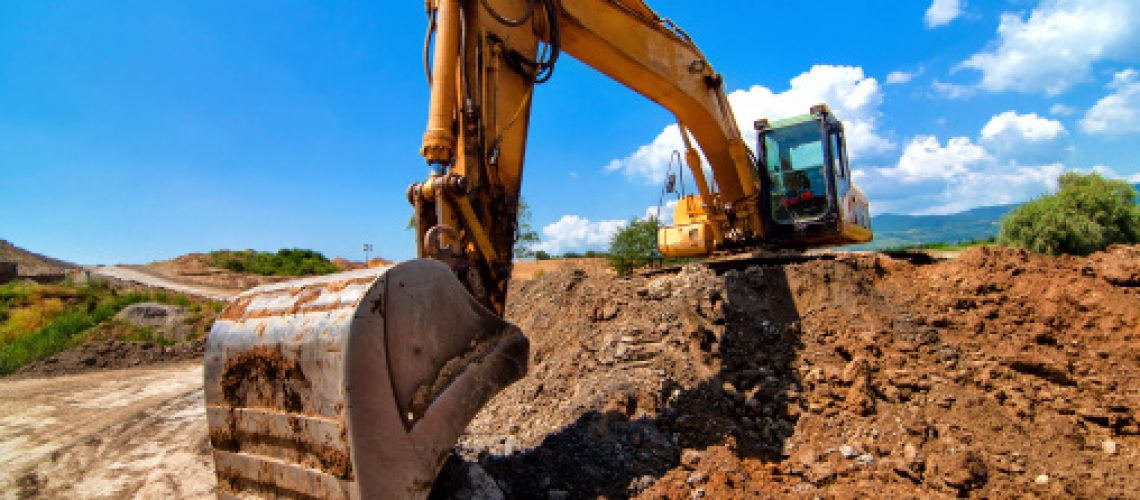 Yellow excavator moving soil and sand on construction site